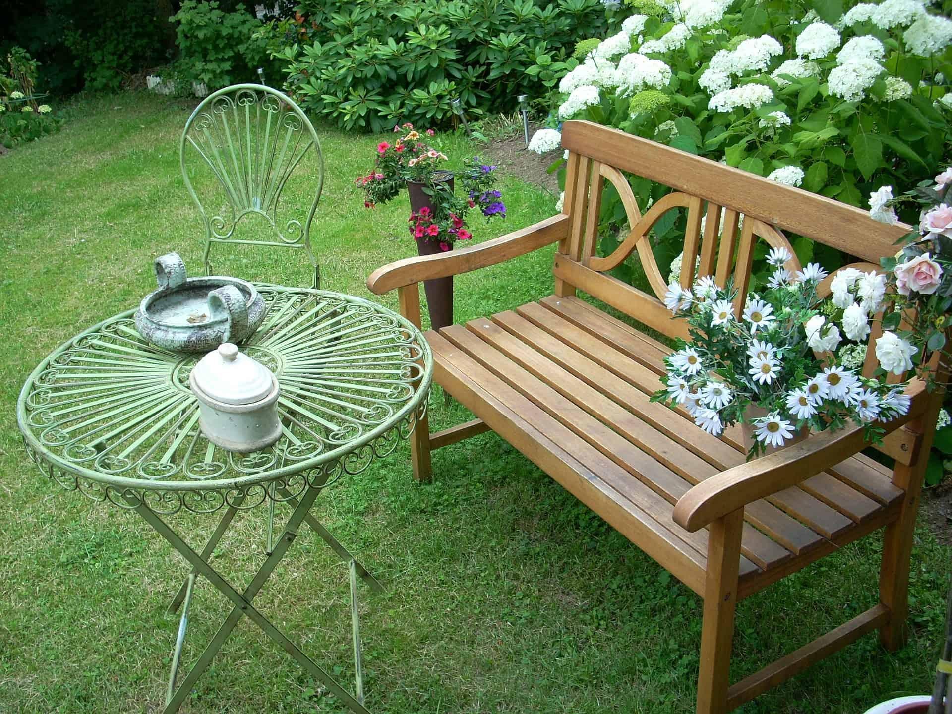 Banco de jardim em madeira próximo a flores, arbustos e pequena mesa de ferro.