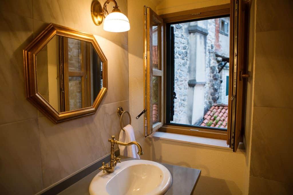 Arandela acesa acima do espelho em um banheiro clássico, com a janela aberta.