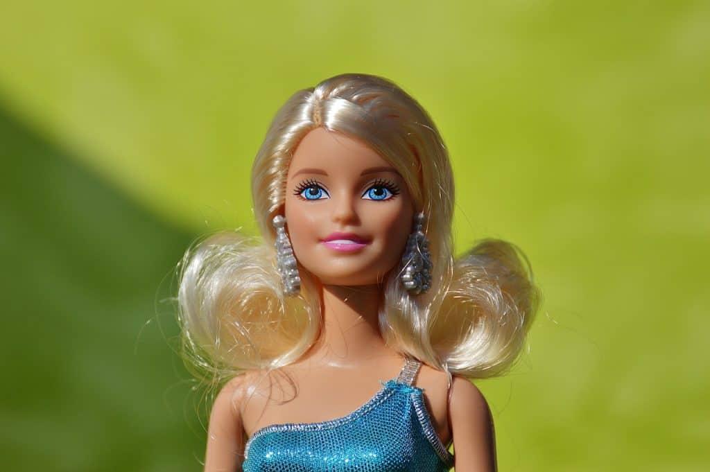 Foto de uma Barbie loira, com uma roupa azul, em um fundo verde, com blur.