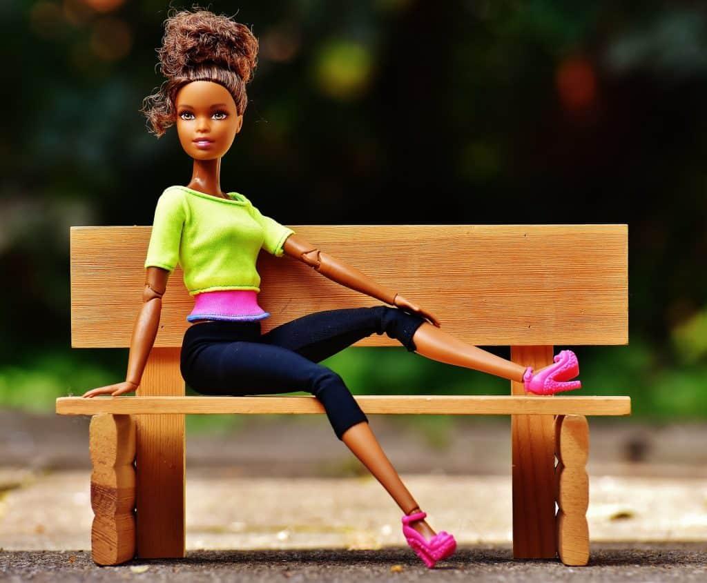 Foto de uma Barbie negra, com blusa verde neon, calça preta e sapato rosa, sentada em um banco.