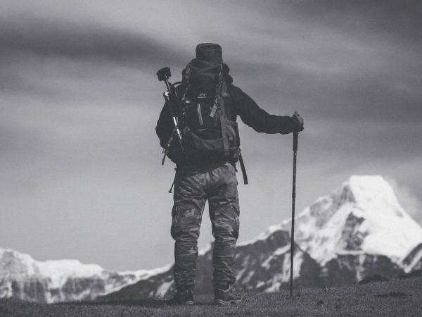 Imagem mostra uma pessoa, de costas para a câmera, observando a vista de um pico de montanha, enquanto apóia-se em seu bastão de caminhada.