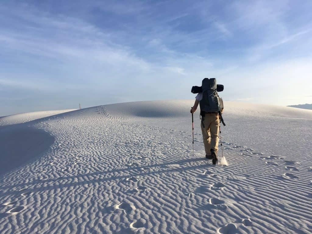 Imagem mostra uma pessoa fazendo uma caminhada em um deserto. Ela sobe uma duna, usando um par de bastões de caminhada.