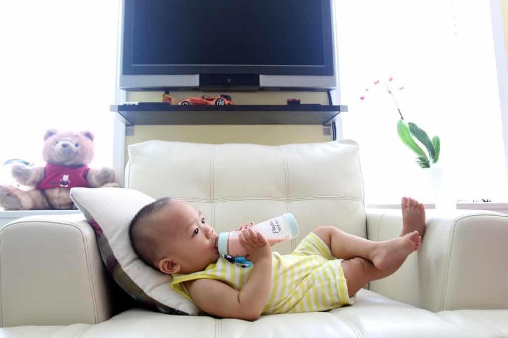 Imagem de criança com roupa listrada em amarelo, deitada sobre sofá, mamando em mamadeira.
