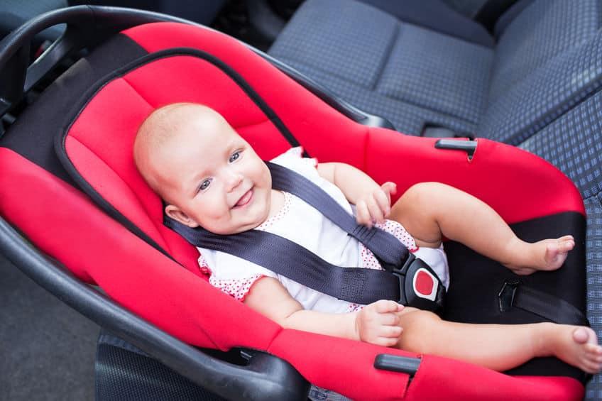Bebê em cadeirinha de bebê para carro sorrindo.