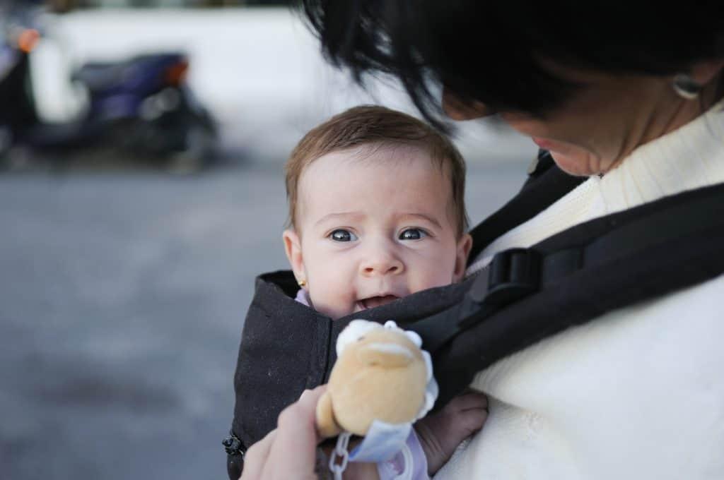 Bebê sorri em canguru enquanto mãe brinca com ele com ursinho de pelúcia.