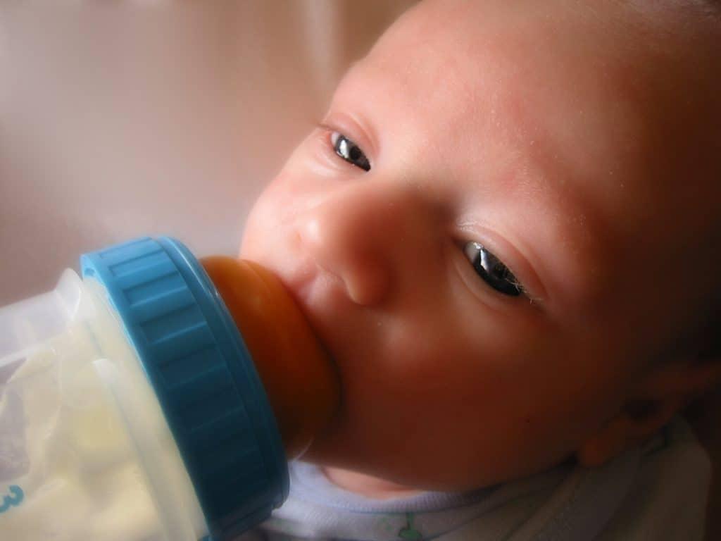 Imagem de bebê sendo amamentado com mamadeira anticólica.