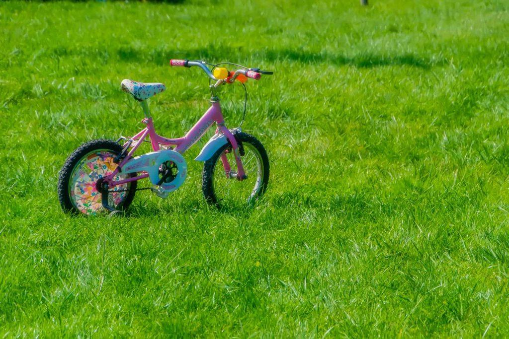 Bicicleta infantil feminina em um gramado.