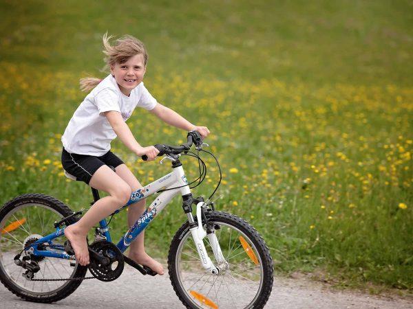 Na imagem está uma menina com shorts e camiseta descendo uma rua de terra em cima de uma bicicleta.
