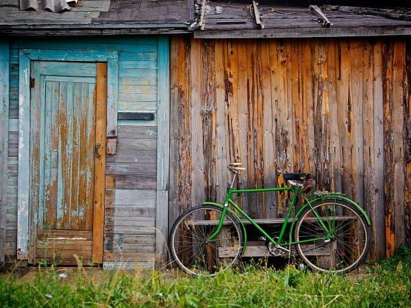A imagem mostra uma casa simples de madeira, com um gramado e uma bicicleta verde encostada perto da entrada.