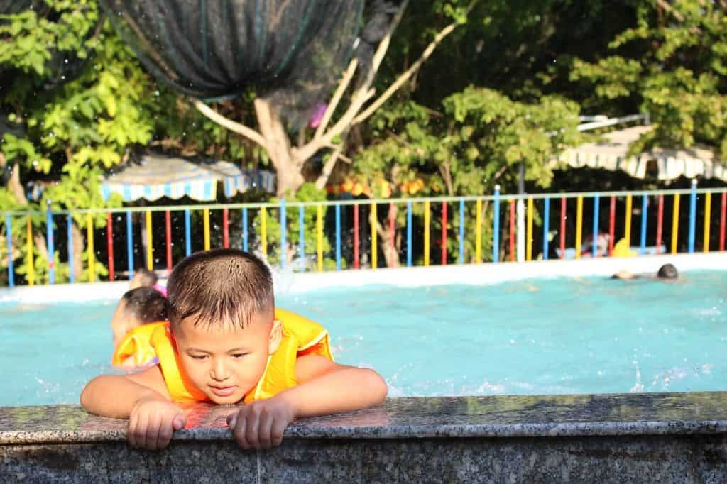Menino usando boia colete tentando sair da piscina.