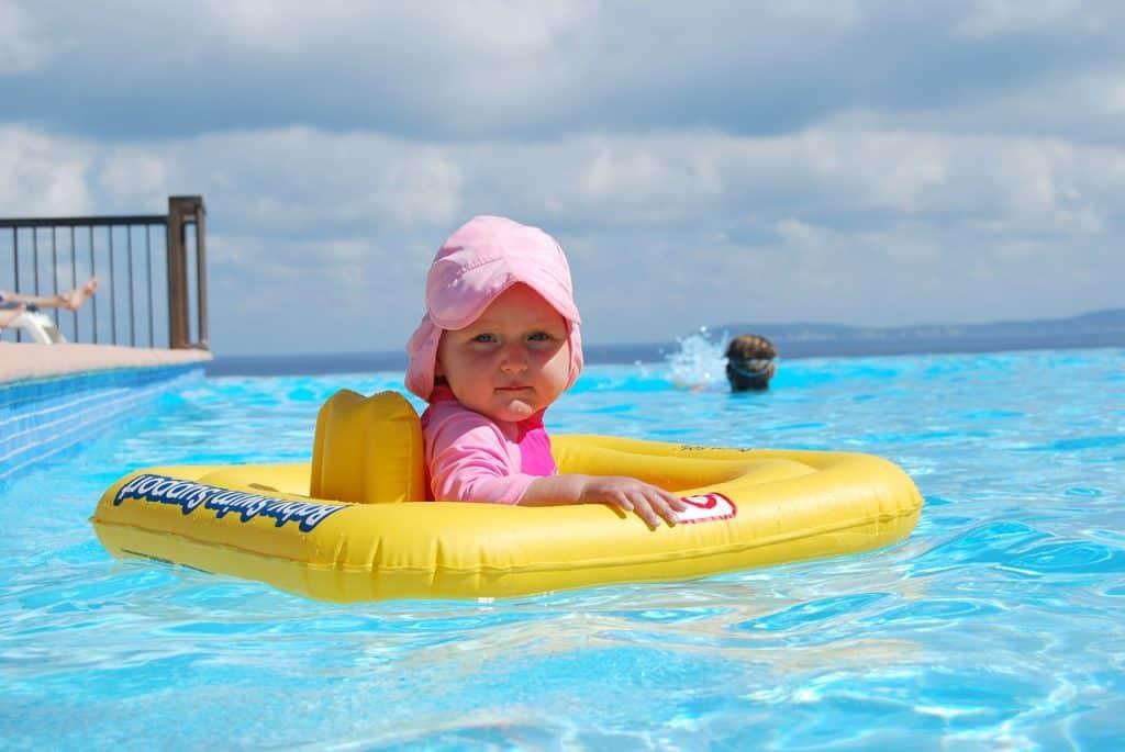 Bebê sentada em uma boia amarela em um piscina de borda infinita.