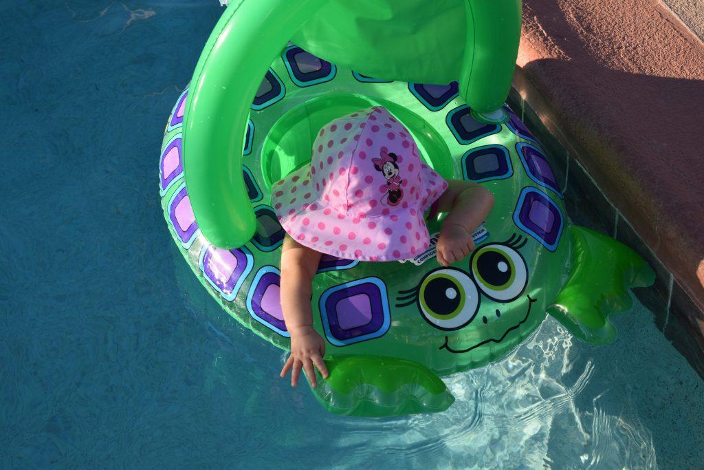 Na imagem uma bebê usando um chapéu rosa da Minnie dentro de uma boia de sentar com tema de sapo.