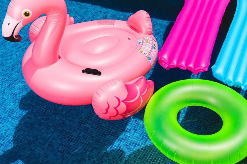 Na foto está uma boia grande em formato de flamingo, um boia circular e duas boias do tipo esteira dentro de uma piscina.