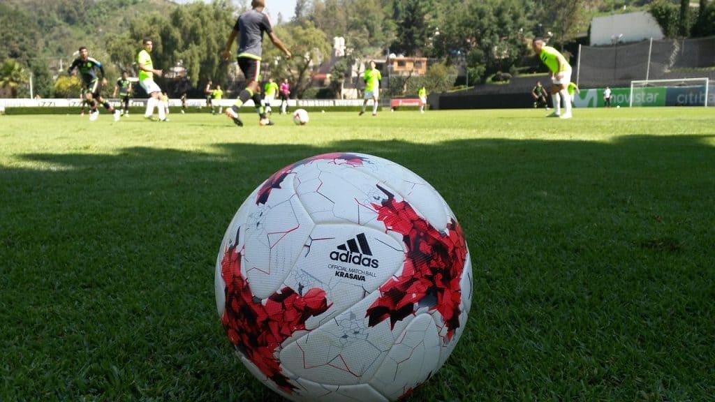 Imagem de bola de futebol adidas com detalhes em vermelho em campo de futebol.