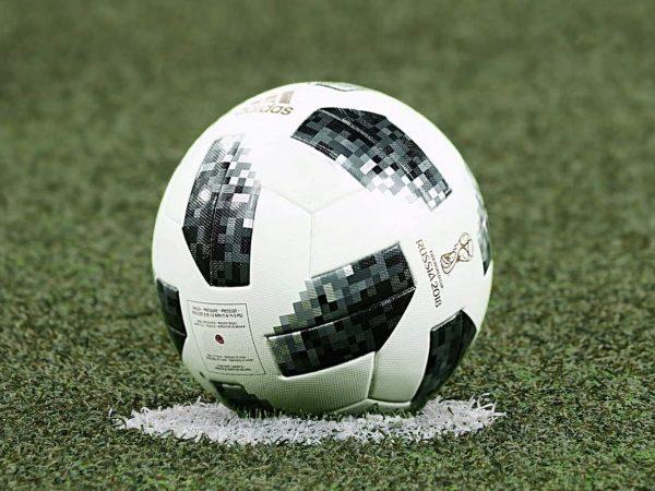 Imagem destaca um gramado de campo de futebol com uma bola de futebol adidas posicionada sobre a marcação.