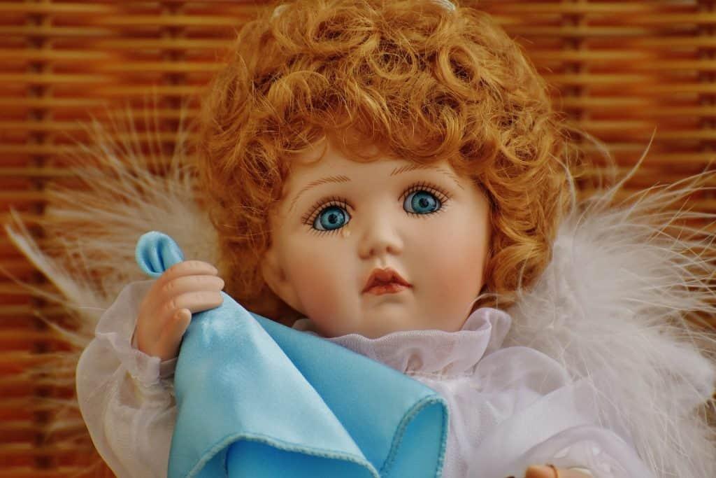 Foto de uma boneca de porcelana, chorando, com trajes e aparência de anjo.