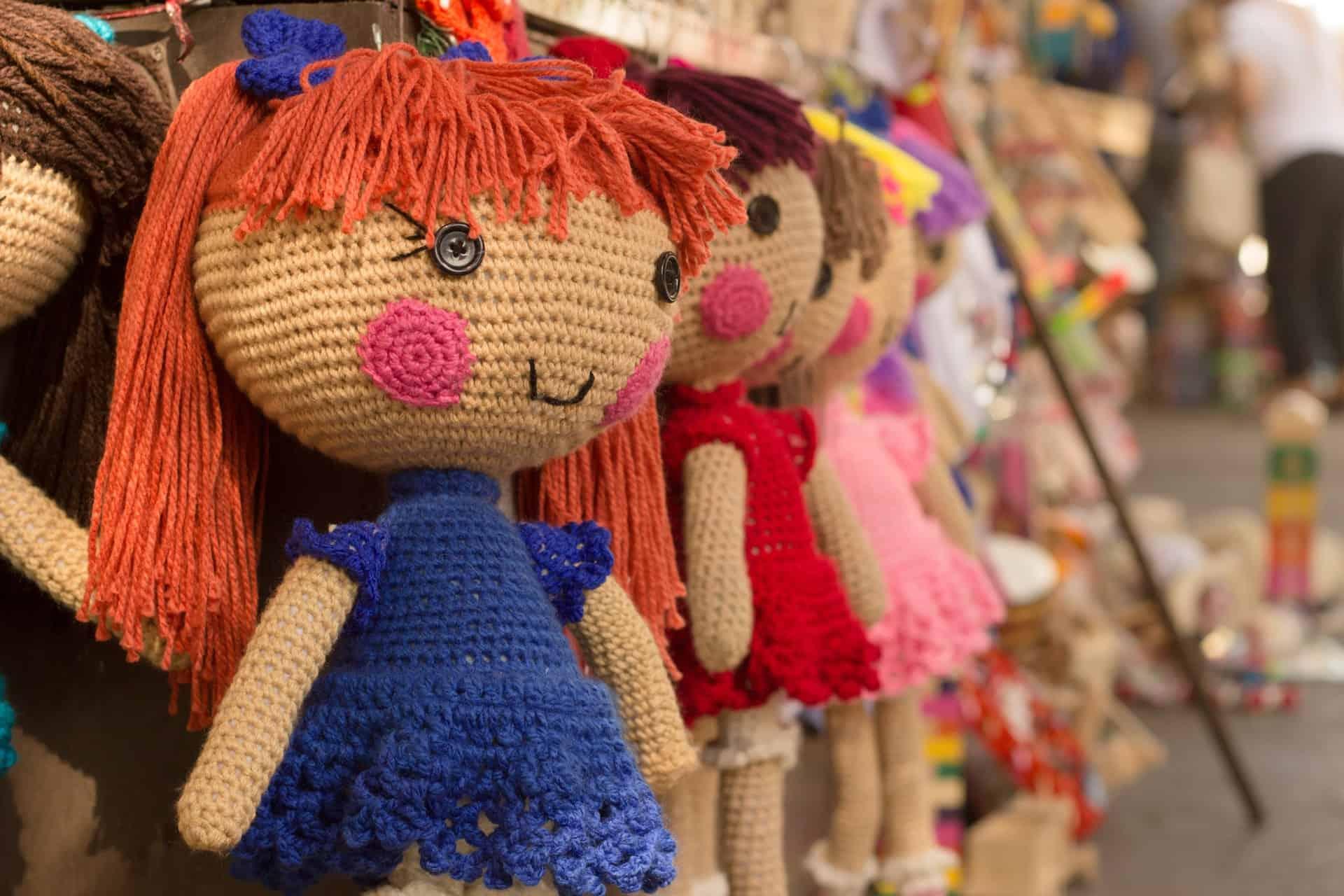 Foto com bonecas de pano bem coloridas penduradas para venda em uma loja.