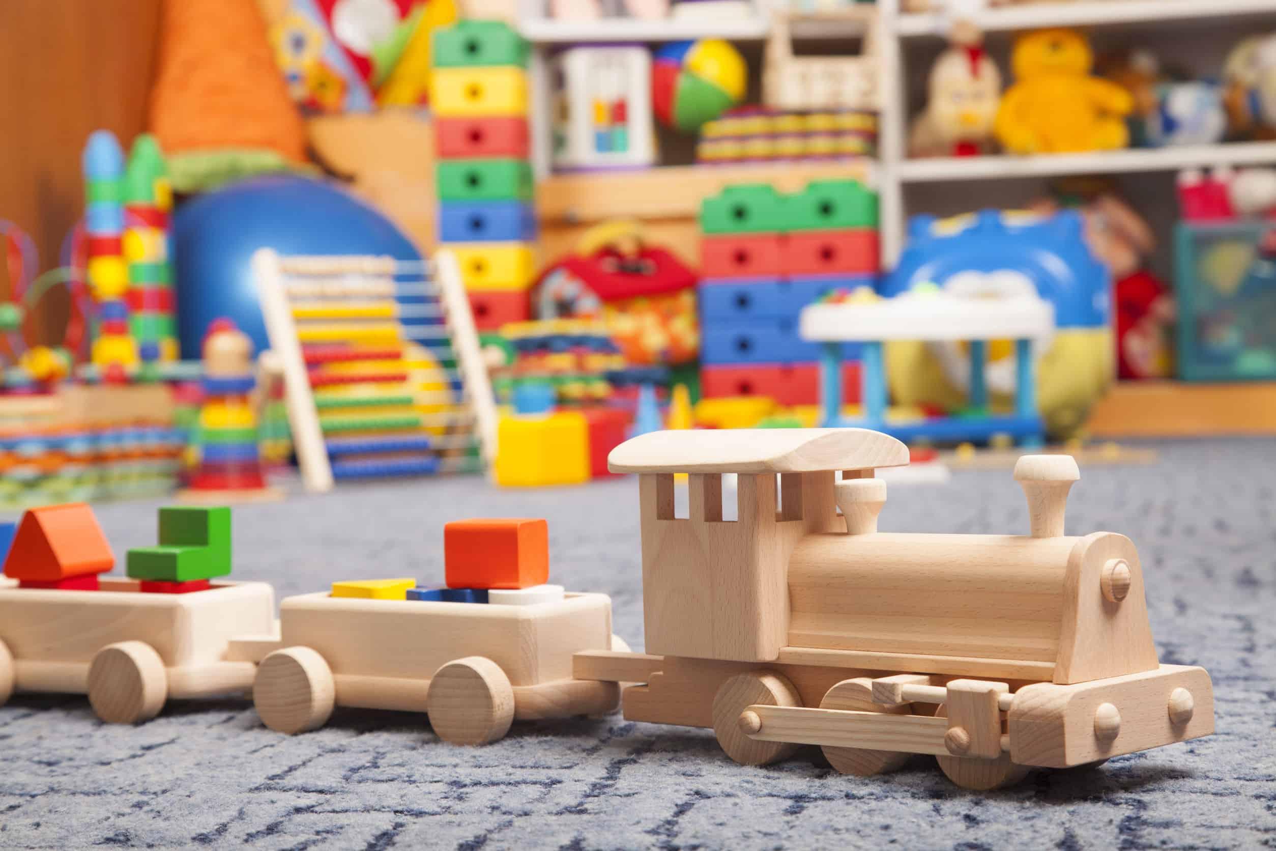 Na foto um trenzinho de madeira com diversos brinquedos de madeira ao fundo.