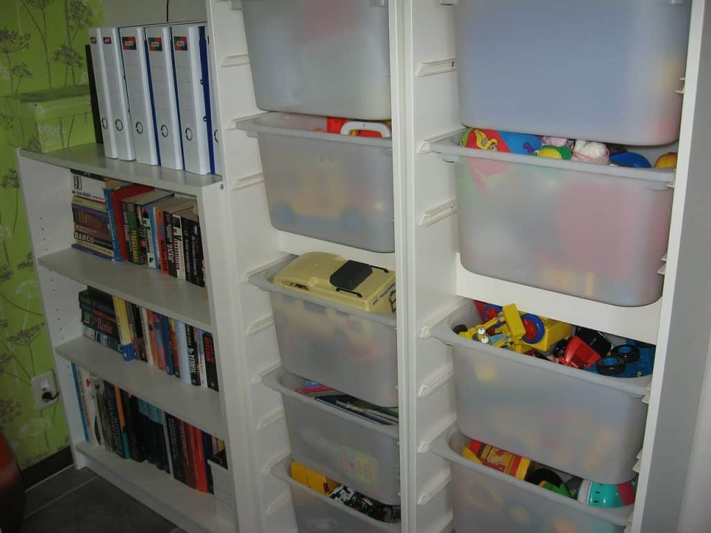 Prateleira com organizadores de brinquedos e estante com livros.