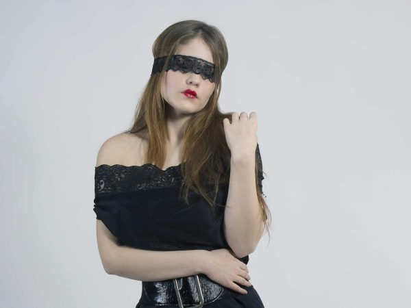 Imagem de mulher com cinta de couro e vestido preto usando uma venda rendada.