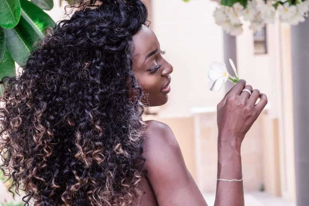 Foto de uma mulher negra de lado, segurando uma flor, com os cabelos bem à mostra.