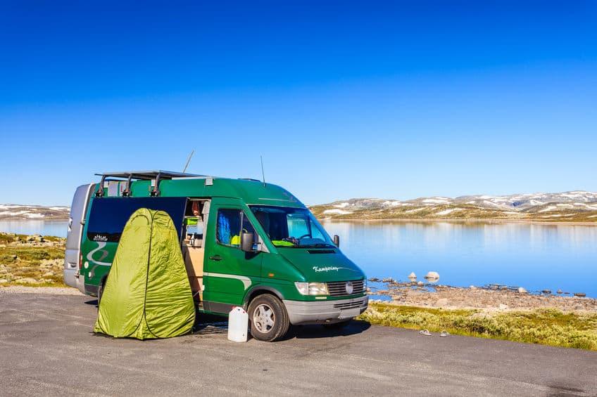 Imagem de van em camping com cabine de chuveiro portátil.