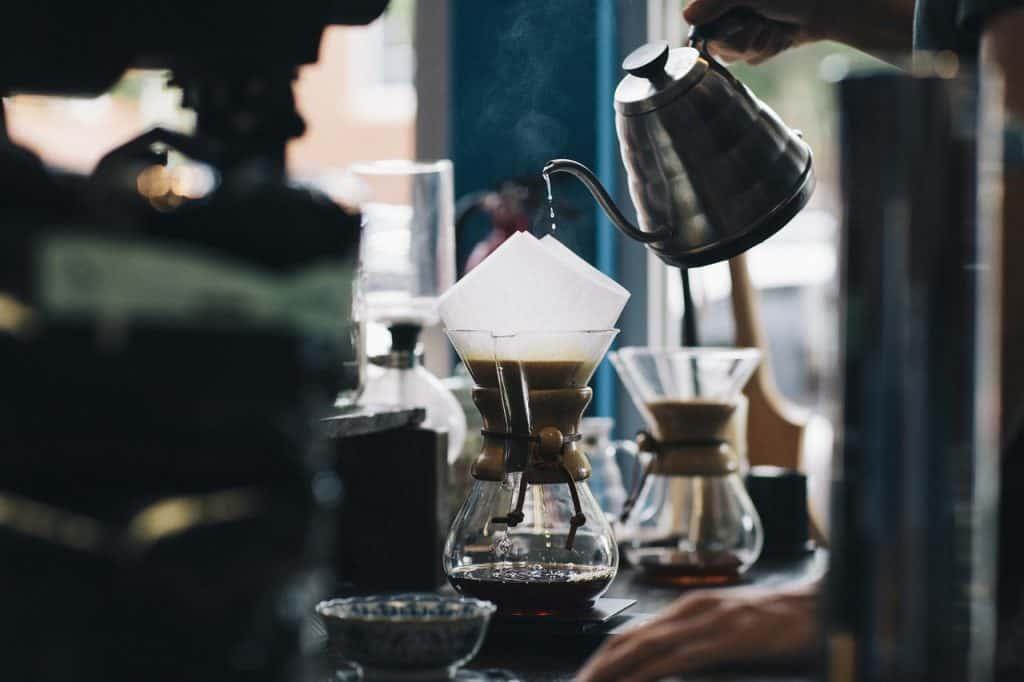 Café sendo coado diretamente em jarra de vidro com uso de filtro de papel.