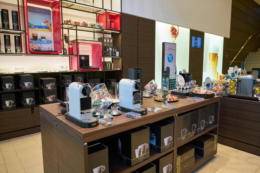Imagem de loja nespresso com cafeteiras sobre mesa.