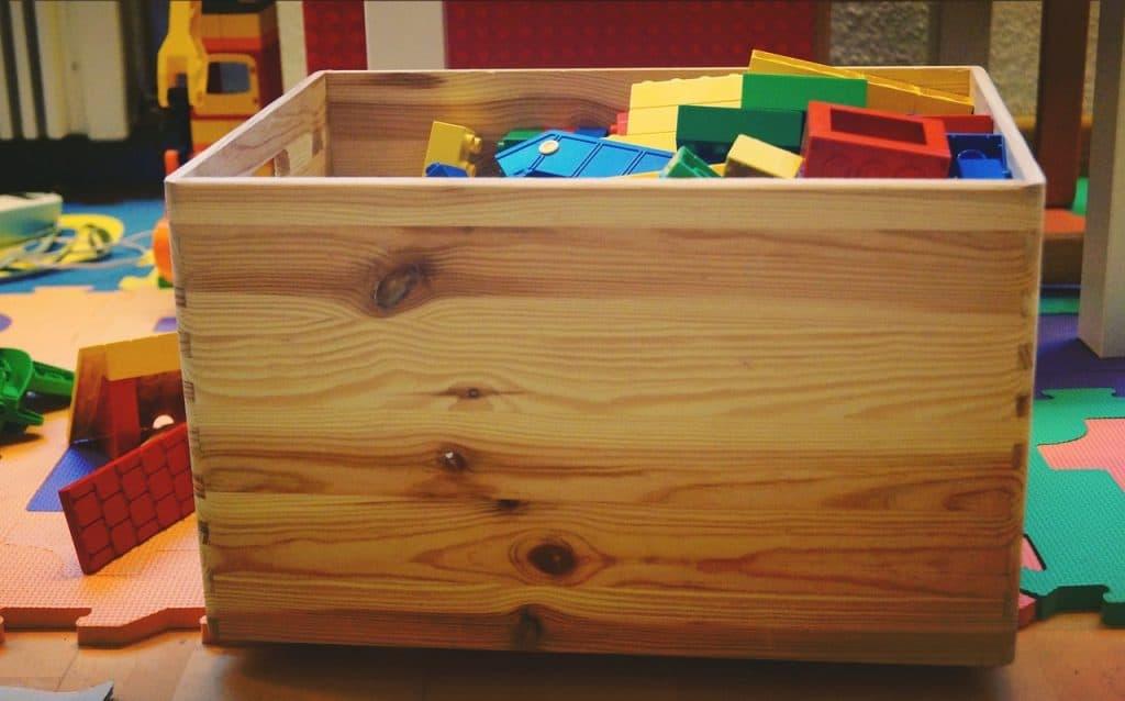 Caixa de madeira com brinquedos.