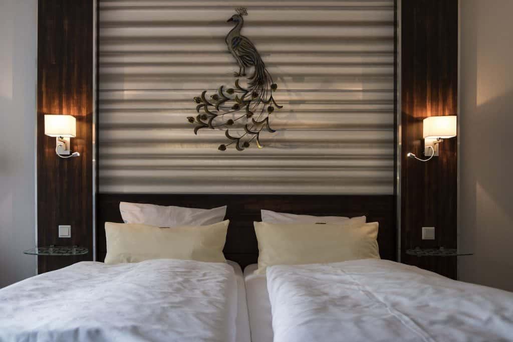 Quarto de casal, com cama e duas arandelas acima do criado mudo.