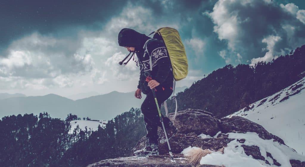 Imagem mostra um rapaz fazendo trekking em uma montanha com uma considerável manta de gelo. Em sua mão esquerda, um bastão de caminhada anti-choque.