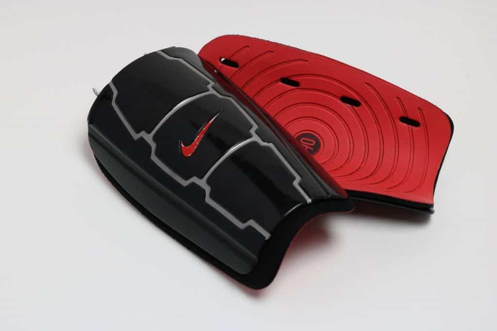 Imagem de caneleira simples preta e vermelha.