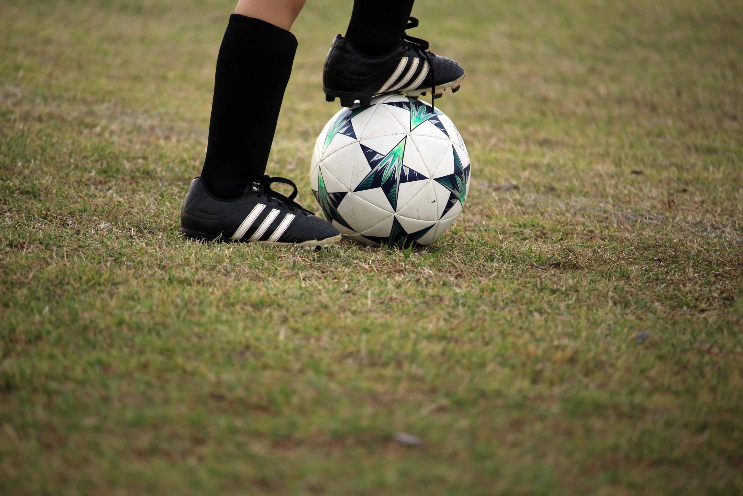 Imagem mostra um par de pernas, com recorte abaixo do joelho. As canelas são cobertas por meiões com uma clara distinção do volume da caneleira. Os pés calçam chuteiras pretas; o pé direito domina uma bola de futebol com a sola.