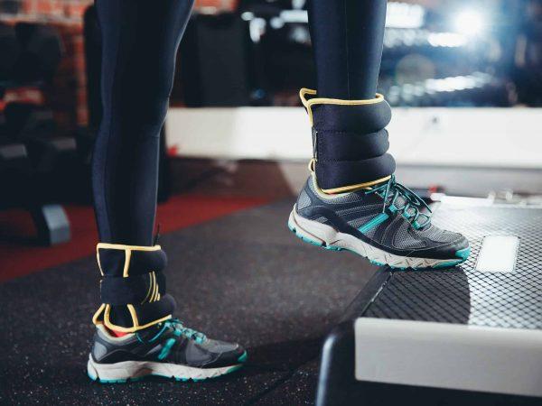Na imagem uma parte das pernas de uma mulher se exercitando com caneleira de peso.