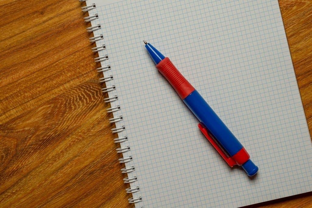 Imagem de caneta esferográfica preta e vermelha com ponta retrátil sobre caderno com folhas quadriculadas.