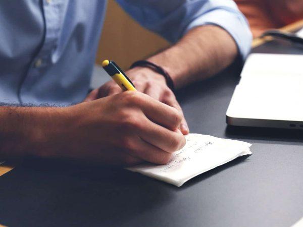 Imagem homem escrevendo com uma caneta esferográfica amarela e preta com ponta retrátil.