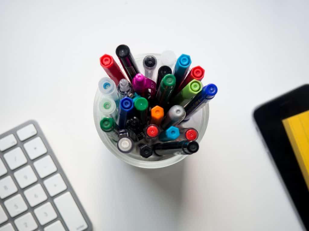 Imagem de porta caneta com canetas coloridas dentro.