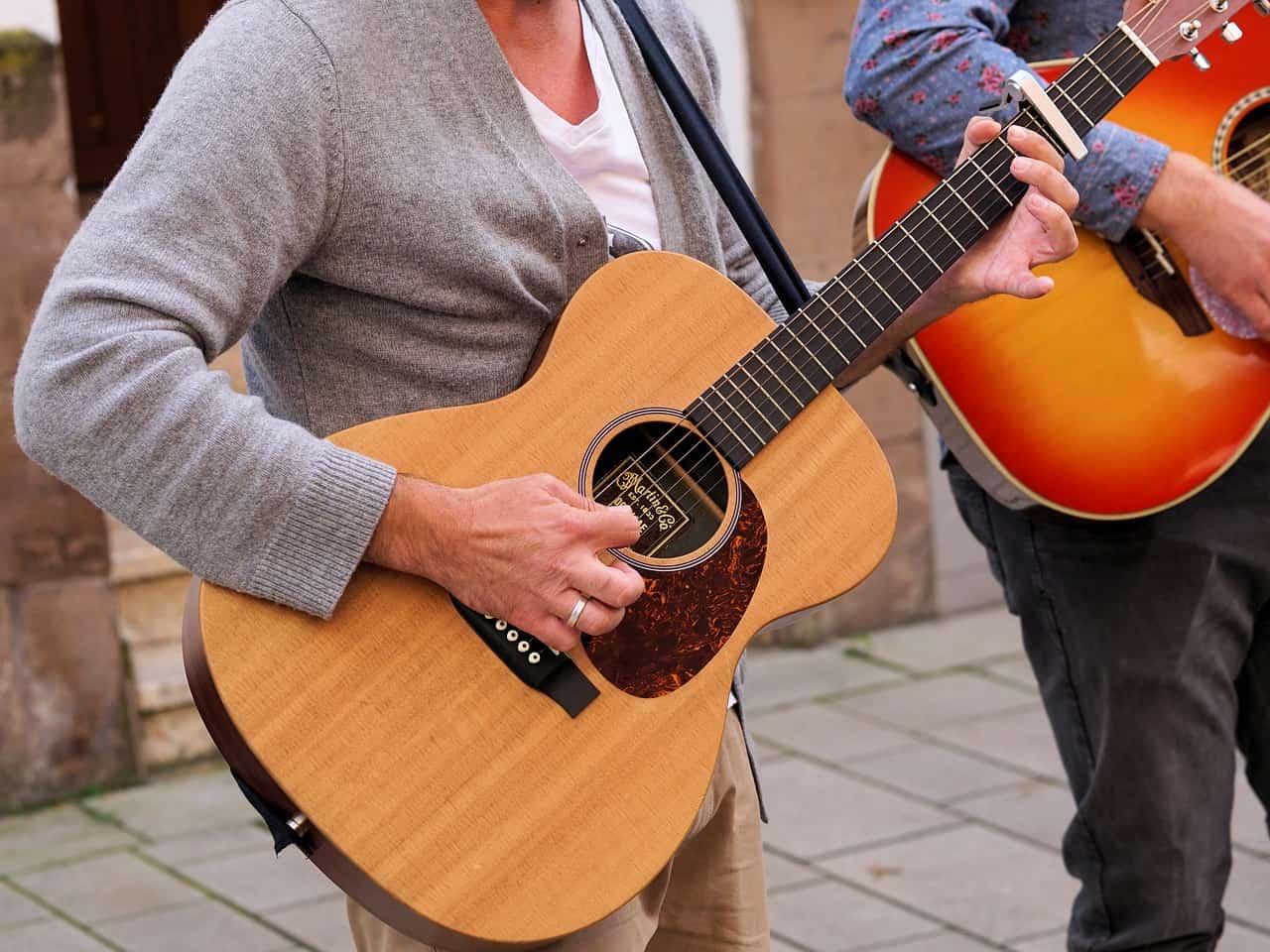 Um homem tocando um violão com corda de nylon usando capotraste na terceira casa, ao lado dele tem outro homem também tocando violão. Os dois homens estão em uma calçada.