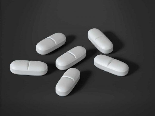 seis comprimidos brancos espalhados com um fundo preto
