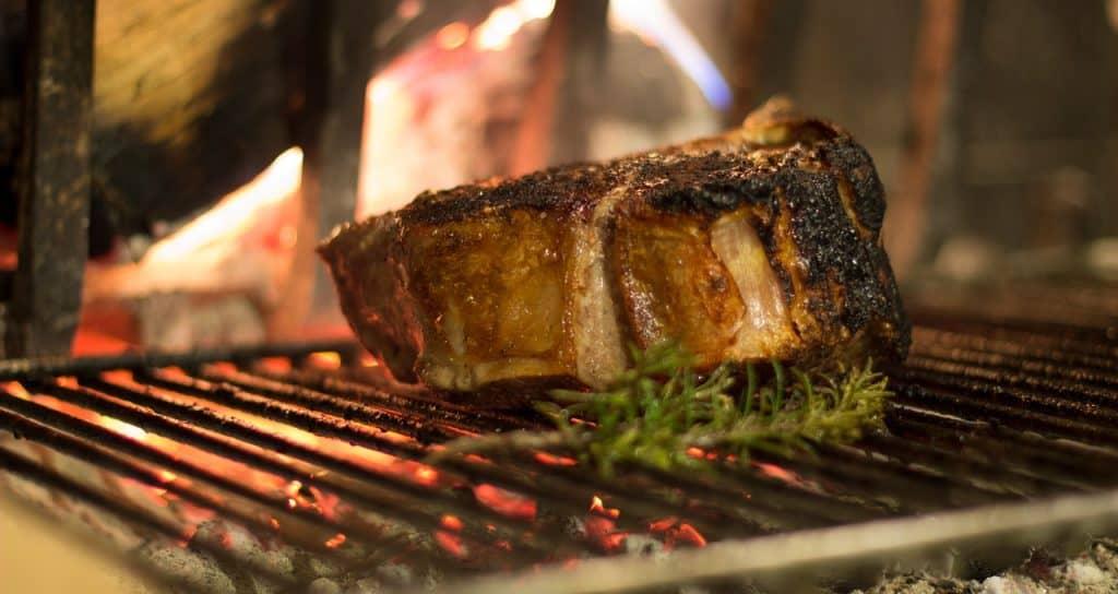 Na imagem há um pedaço de carne dentro de uma churrasqueira.