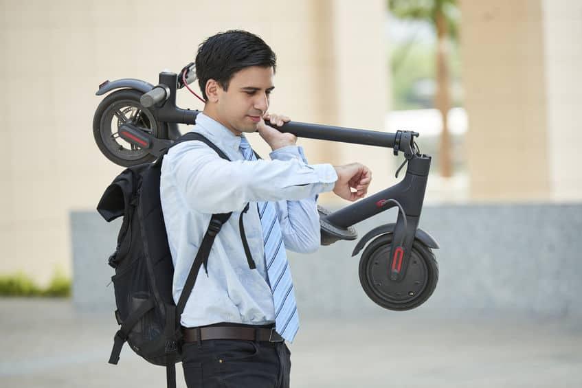 Imagem de homem com terno carregando seu patinete elétrico.