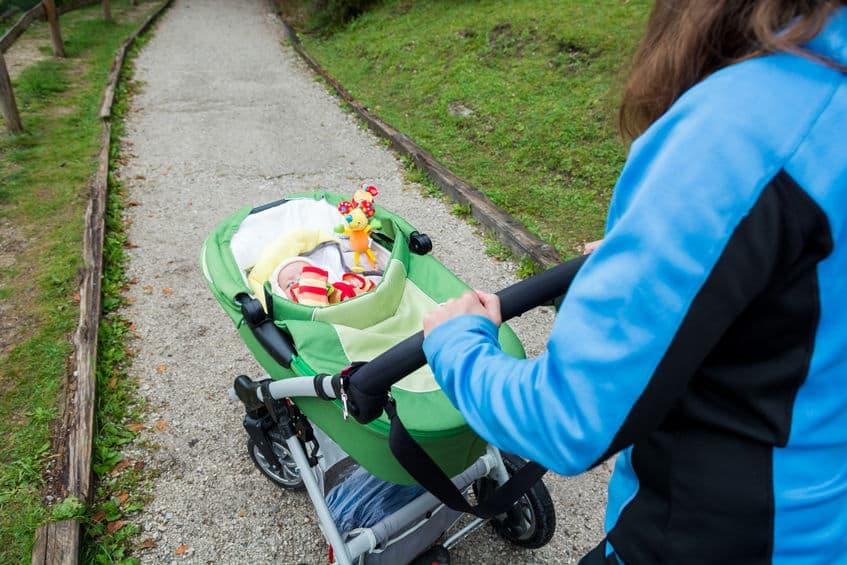 Imagem de mãe puxando carrinho com seu bebê, que está brincando com móbile.