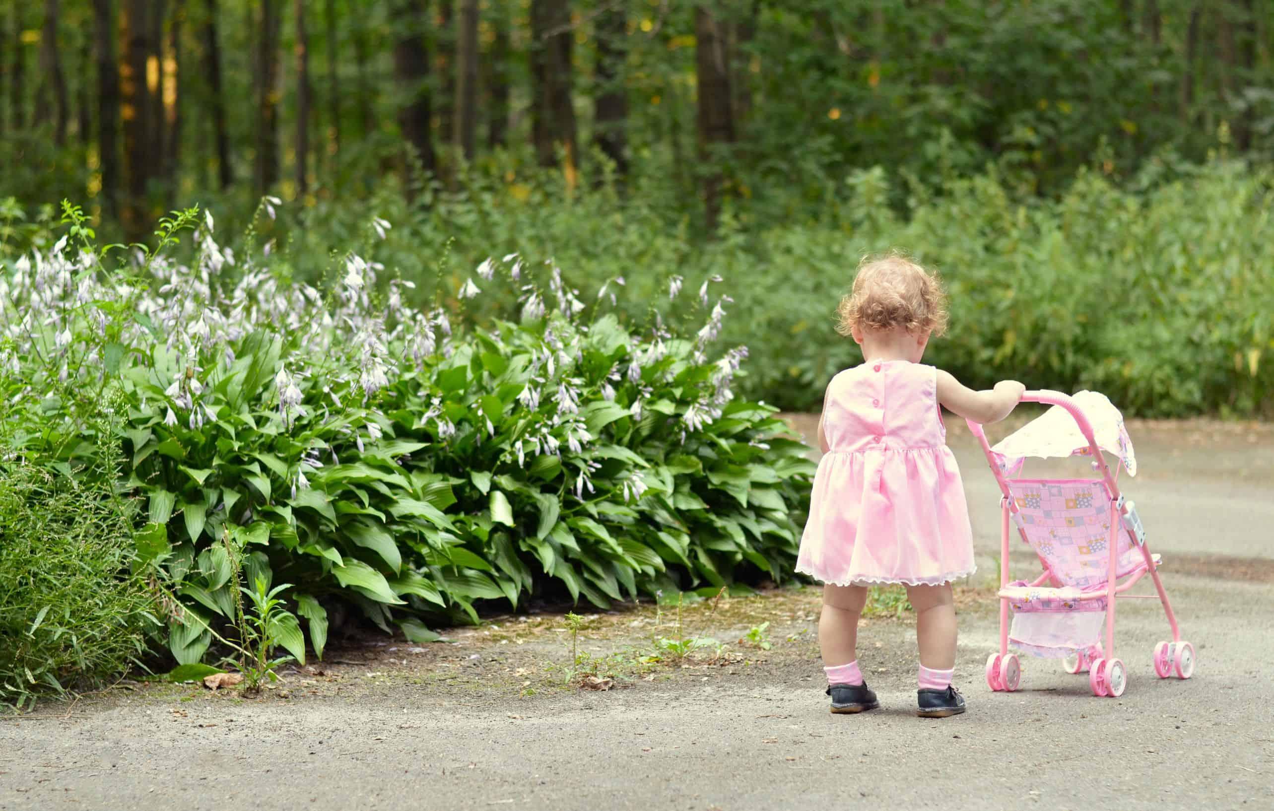Criança empurrando carrinho de boneca.