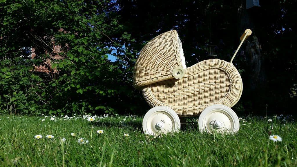 Carrinho de boneca de palha, sobre a grama.