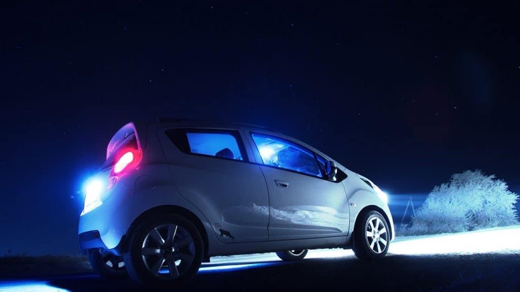Imagem de carro branco com farol ligado a noite.