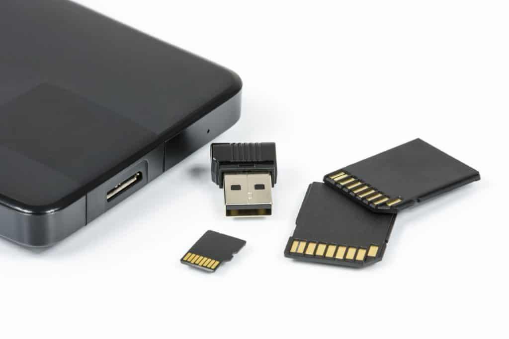 Imagem de um HD externo, nano pen drive e três cartões de memória.