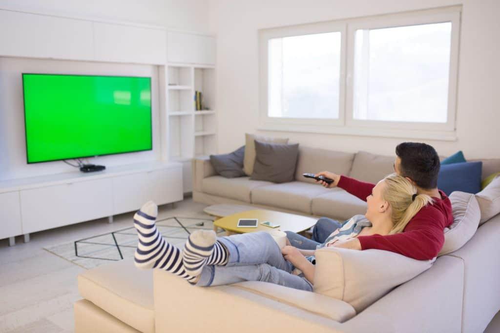Casal sentado no sofá da sala assistindo televisão de 65 polegadas.