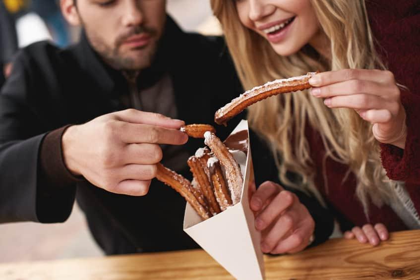 Casal comendo churros juntos.