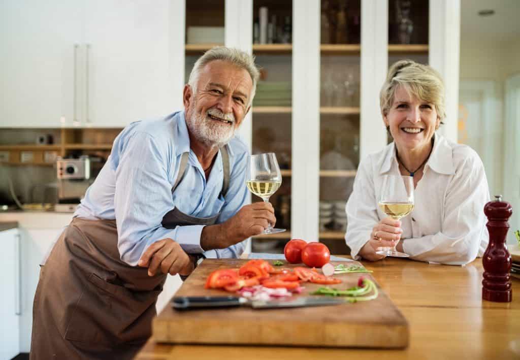 Na foto um casal de idosos dentro de uma cozinha com uma taça de vinho nas mãos e uma tábua com legumes na frente.