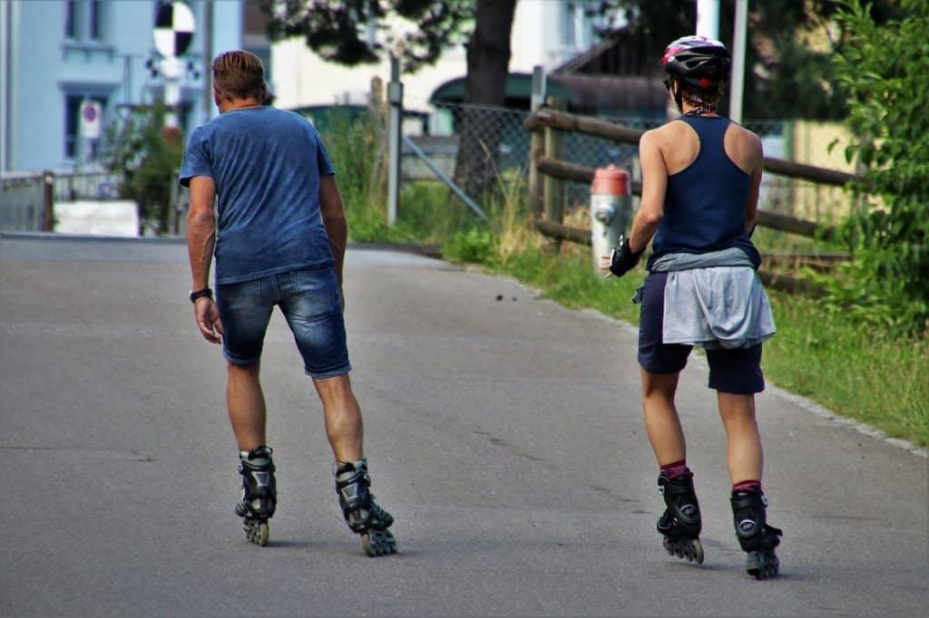 Imagem de homem e mulher andando juntos com patins inline na rua.